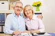 Glückliches Paar Senioren am Schreibtisch