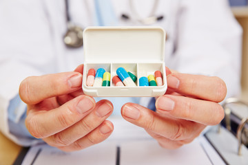Arzt zeigt Pillenbox mit Medikamenten