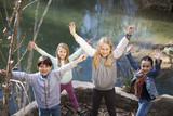 Niños junto a río levantando los brazos