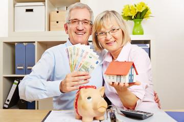 Paar Senioren mit Geld und Haus und Sparschwein