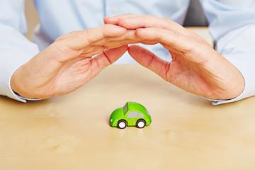 Zwei Hände schützen kleines Auto