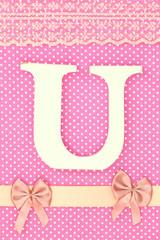 Wooden letter U on polka dots background