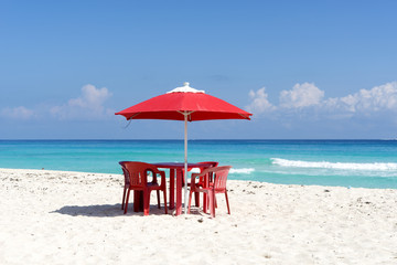 Chairs, table and umbrella on a tropical beach in Cancun, Mexico