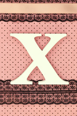 Wooden letter X on polka dots background