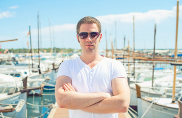 Man portrait against of the pier with yachts.