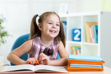 cute smiling kid reading book in children room