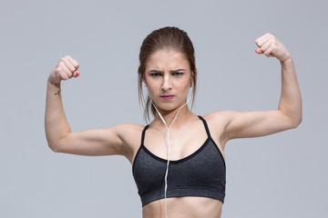 Portrait of young woman flexing her biceps over gray background