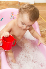 Cute little girl bathes in a shower