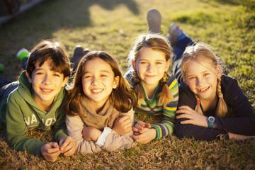 Niños tumbados sobre la hierba sonriendo