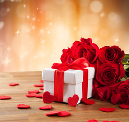 Gift with roses on wooden table
