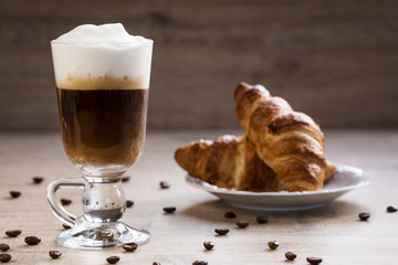 a cup of cappuccino with croissant