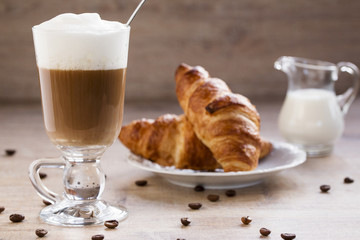 a cup of cappuccino with croissant and milk