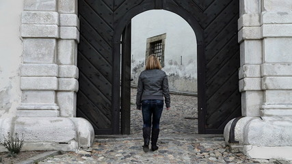 Shot of a woman walking out of castle