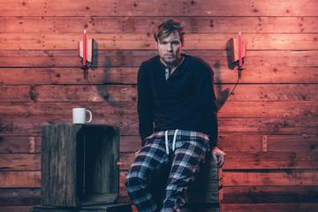Man with blonde hair and beard wearing winter sleepwear. Sitting