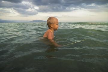 Little boy bathes in the sea