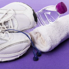 Fitness background, sneakers, headphones, water bottle and towel