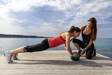 Young woman doing push-ups on a medicine ball with a coach