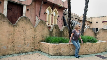 Woman passing by and ancient city buildings
