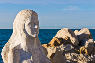 Mermaid sculpture carved out of rocks at Piran harbor, Istria