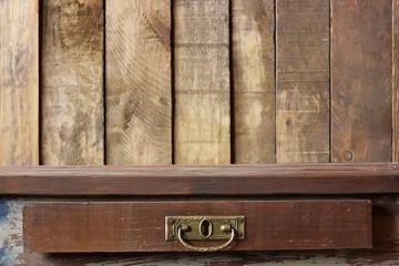 Деревянный стол с ящиком на фоне стены из досок