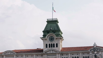 Clock tower with waving italian flag at the top