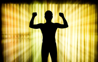 Silhouette man show his muscle with light ray effect