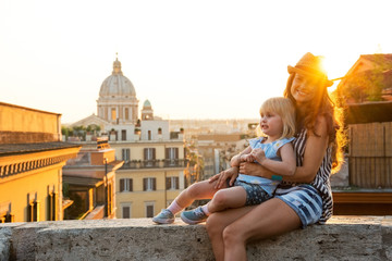 Mother and baby girl sitting on street  in Rome