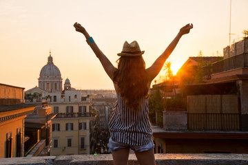Young woman looking on rooftops of rome on sunset and rejoicing.