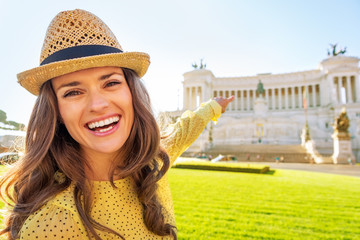 Portrait of happy young woman pointing on piazza venezia in rome