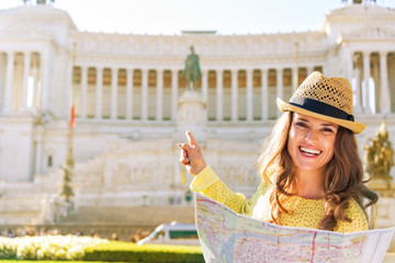 Happy young woman with map pointing on piazza venezia in rome