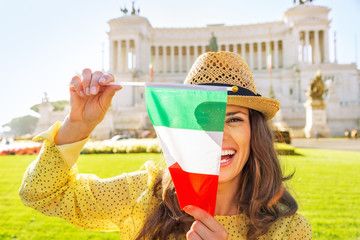 Happy young woman showing italian flag on piazza venezia in rome