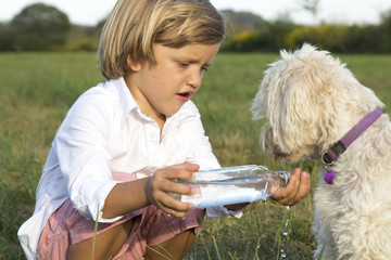 Young cute boy giving water  to his dog