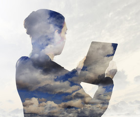 Woman with digital tablet composited with images of clouds
