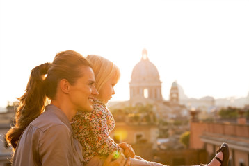 Mother and baby girl looking on rome panorama on sunset