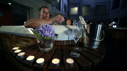 night of wooden jacuzzi outside of fancy spcenter that is decorated with big purple flowers