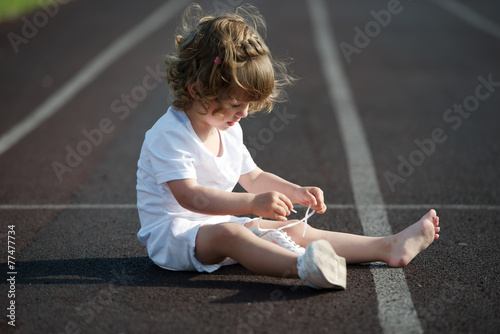 canvas print picture beautiful little girl learning to tie shoelaces
