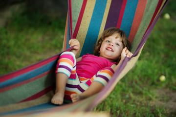 little girl resting lying on hammock