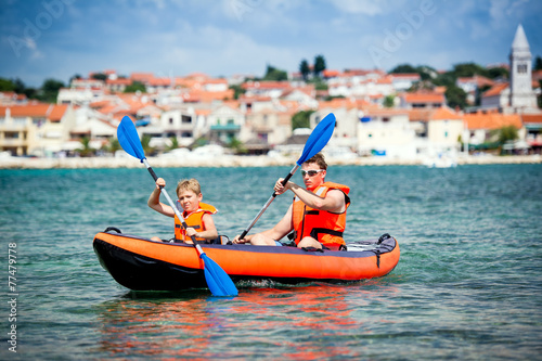 father and son in a kayak - 77479778