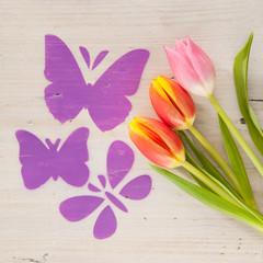 Schmetterlinge fliegen über eine Tulpenwiese