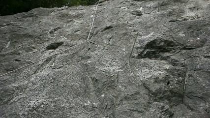 Young man rock climbing in nature