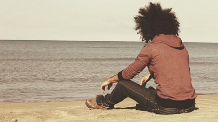 Sad lonely man sitting on the beach