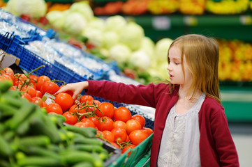 Little girl choosing tomatoes in a store