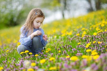 Adorable girl in blooming dandelion flowers