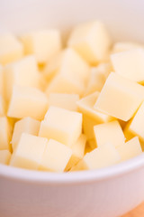 cheese cubes close up on wooden background - selective focus
