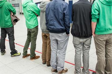 Junge Männer warten vor der roten Linie - Schüleraustausch