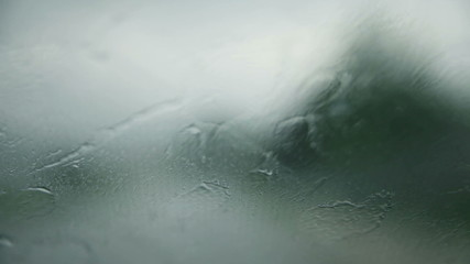 Extreme close up on rain drops on windshield while driving