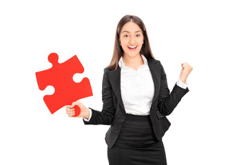Delighted businesswoman holding a piece of puzzle
