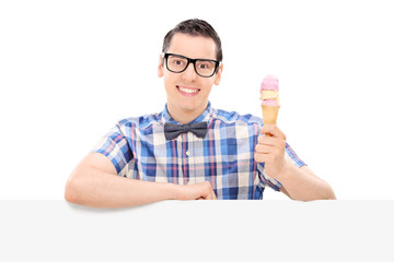 Cheerful guy holding an ice cream behind a panel
