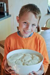 Junge ist stolz auf seinen allein gemachten Brotteig