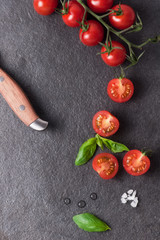 Halved cherry tomatoes and basil leaves on black slate